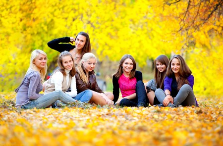 many young girls in the autumn park sitting on the grass photo