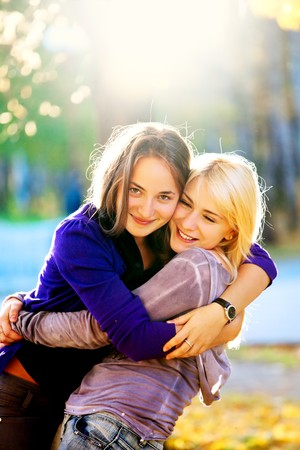 two beautiful teenage girls hugging in the autumn park