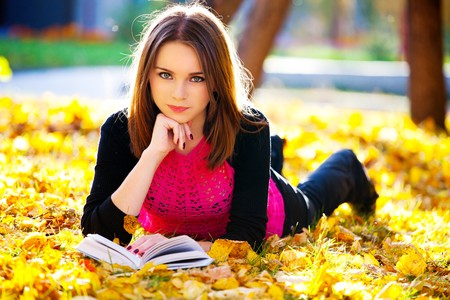 beautiful girl with book in the autumn park photo