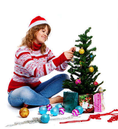 beautiful woman in christmas hat decorates a christmas tree photo