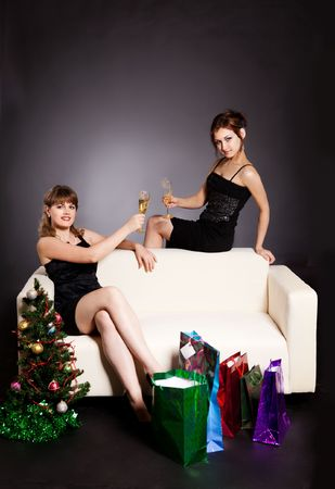 two women celebrate christmas in evening dress photo