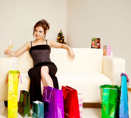 young woman sitting on the sofa with shopping bags photo