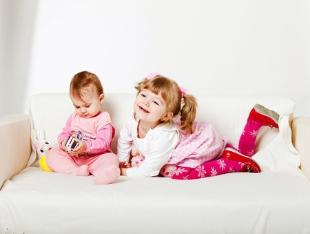two adorable kids sitting on the sofa Stock Photo