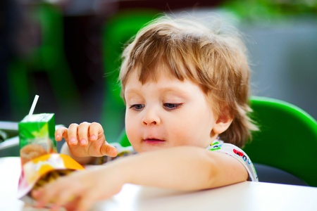 chear: little child eating fust food in the cafe Stock Photo