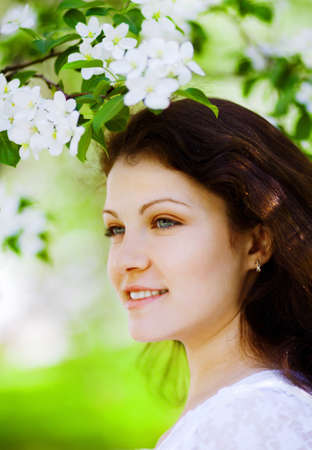 portrait of beautiful woman in the flowering park photo