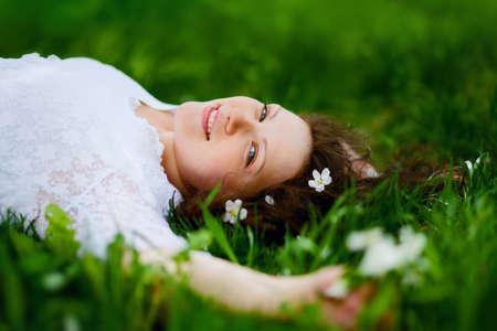 portrait of beautiful woman lying on the grass photo