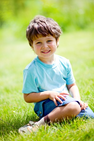 portrait of cute little boy sitting on the grass Stock Photo - 11307566