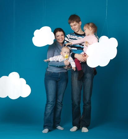 Happy family of four on blue background photo