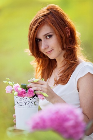 portrait of beautiful young woman with flowerpot in the hands photo