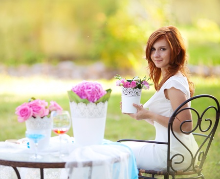 portrait of beautiful young woman with flowerpot in the hands