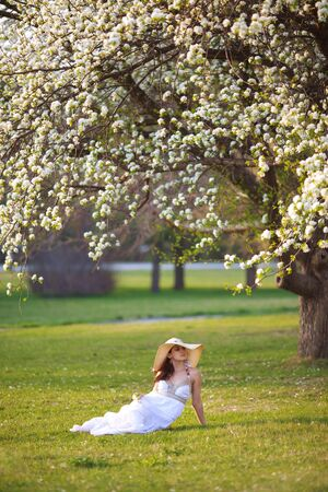 Beautiful woman sitting on the grass in summer park photo
