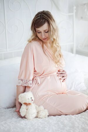 house robe: Beautiful pregnant woman in the pink robe