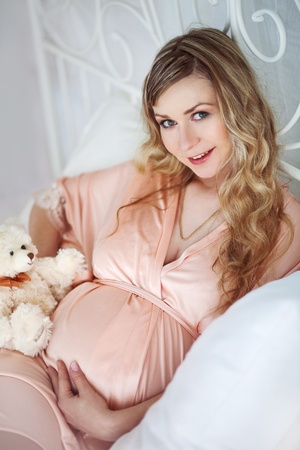 house robe: Beautiful pregnant woman in the bedroom Stock Photo