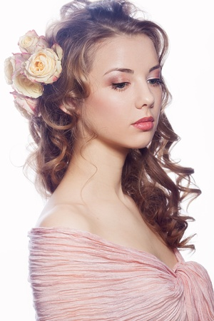 Portrait of beautiful girl with roses in the hair photo