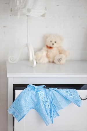 Blue babys clothes in the white childroom photo