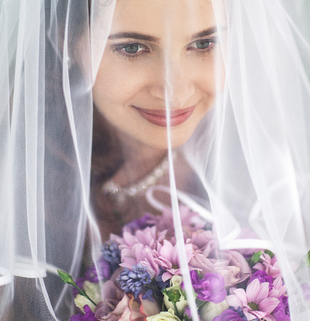 Closeup portrait of beautiful bride under the veil photo