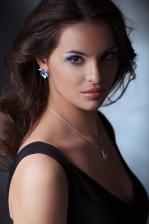 brunets: Face portrait of beautiful woman with blue earrings Stock Photo