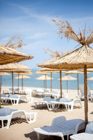 daybed: View of the sand beach with straw parasols