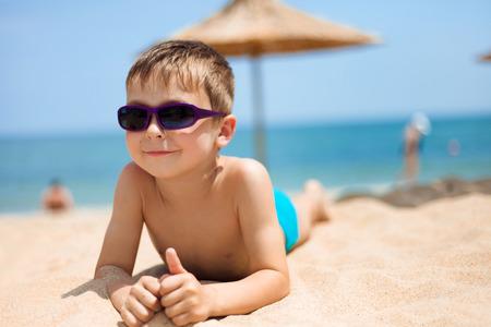 Close-up portrait of little boy on the beach photo