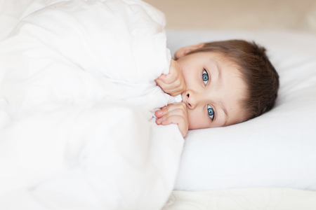 affraid: little boy in the bed sleeping daytime Stock Photo