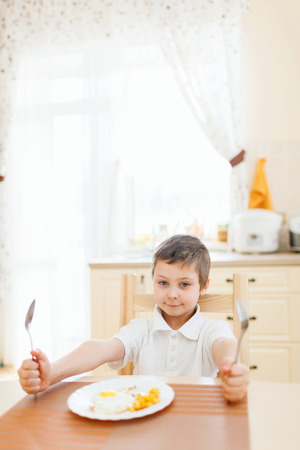 omlet: Portrait of little boy in the kitchen