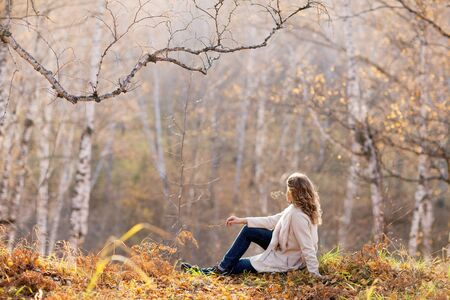 Beautiful woman sitting in the autumn forest photo