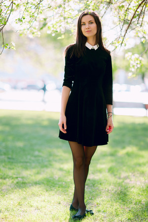 casual wear: Beautiful young woman in casual wear in the flowering park Stock Photo