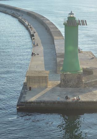 A green lighthouse on a pier