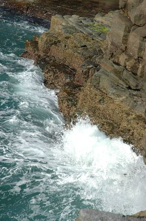 Waves crashing onto rocks, seen from above.