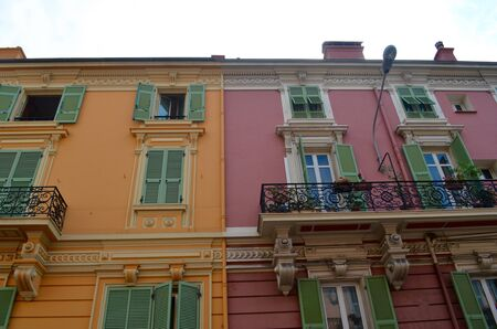 Brightly painted buildings with green shutters and iron railings.