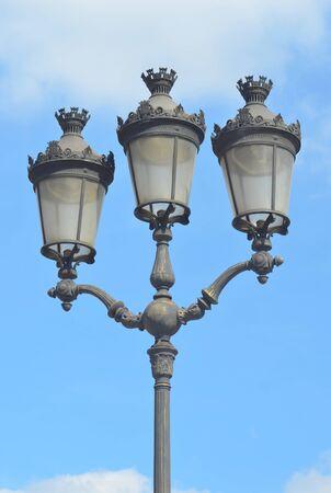 A grey Parisian lamp post against a blue sky