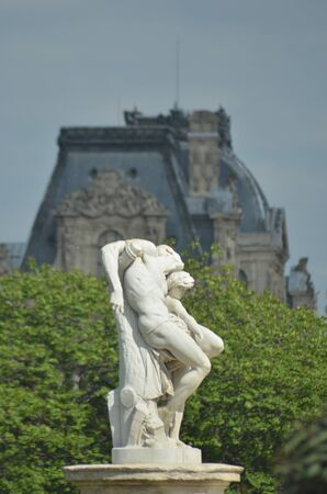 A white marble statue against trees and the backdrop of a typical Paris roofline