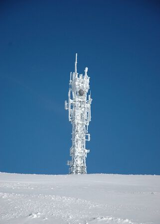 A snow and ice covered telecommunications tower against a clear blue sky. The foreground is untouched snow. Stock Photo