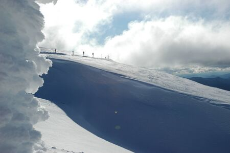 A line of road signs dwarfed by a snow-covered mountain. A snow-covered sign frames the shot. Deep shadows of blue run down the nountain. Hills are in the distance, and the sky is cloudy.
