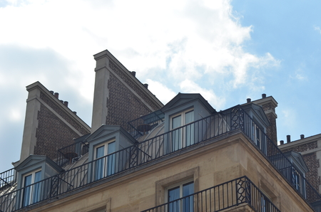 The upperstory and roof line of an apartment block in Paris. Chimneys and walls seperate the individual apartments. The building is brown stone and brick with gray railings. The sky is bue with sith white clouds.