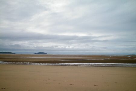 A receding tide has left a large amount of sand exposed on a beach. Some water remains. Two small hills are visible in the distance, and two tankers are just visible on the horizon. The sky is grey and overcast.