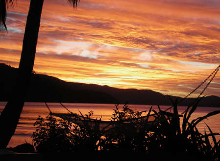 The colours of sunset falling over a bay. Silhouetted palm trees and a hammock are in the foreground, and hills in the distance. The clouds  have turned yellow and orange. Stock Photo