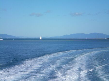 The white wash from a boat spreads across a blue ocean. Other yachts are visible, some with sails. The beach is in the distance, with hills behind. The sky is blue, with a few clouds. A small town can just be seen by the waters edge.