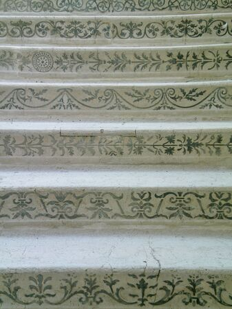 A set of old marble stairs. A variety of green-blue patterns are on the front. The marble is white, and filled with cracks.