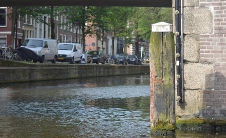 木製ログは、アムステルダムの運河沿いの角をマーキングします。木材は欠けていて、年齢に歪んでいます。レンガの壁の横にある、橋の下のビュ 写真素材