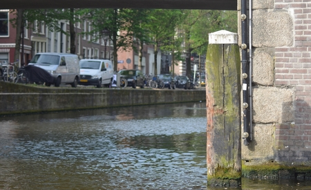 A wooden log marking the corner of a canal in Amsterdam. The wood is chipped and warped with age. It is beside a brick-wall, and the bottom of a bridge frames the view. The image has a shallow depth of field, with the side of the canal and a row of cars,