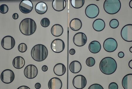 A random pattern of glass circles (similar to portholes) on a door. The door is grey, the circles framed in black. An industrial scene can be glimpsed through the glass Stock Photo