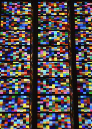 An abstract pattern of small brightly coloured squares in a stained glass window. The colours appear randomly arranged.