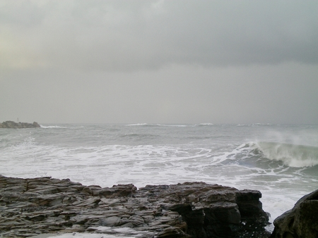 A strom approaching a rcoky shelf on the coast. Waves are breaking. Grey clouds fill the sky.