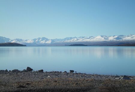 A view across a still blue lake to distant snow-capped mountains. The sky is blue. The shore of the lake is covered in pebbles. The scene is deserted.