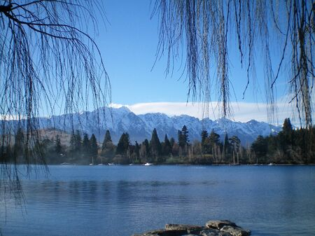 View across a blue lake to distant snow-covered mountains. The bare branches of a tree frame the view. Some boats are moored on the far side of the lake.