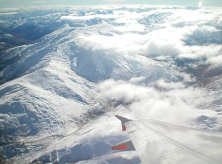 A view over the wing of a plane to snow-covered mountains. The plane is above some white clouds. The peaks of the mountains are just below the clouds.