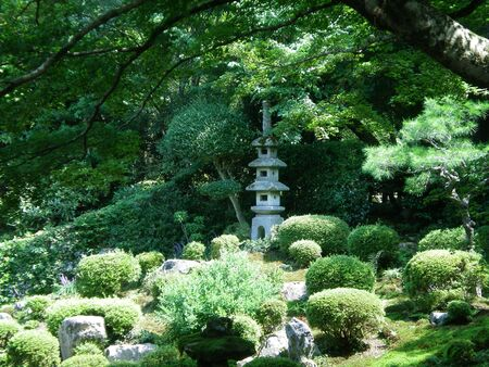 A Japanese stone shrine in a typical formal garden. It is surrounded by small pruned green shrubs and rocks. A tree overhangs the garden. Stock Photo