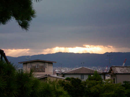 A row of Japanese houses, with the city in the background and mountains behind them. A storm is passing over, but rays of sunshine are breaking through the clouds in the distance. It is close to sunset.
