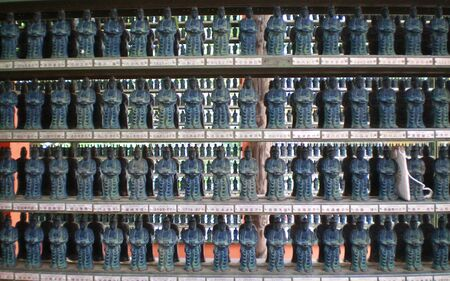 Hundreds of Japanese religious statues displayed on shelves. The statues are small, grey-black in colour, and identical.